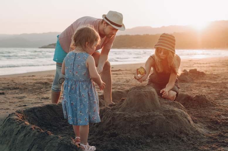 happy family having fun together on the beach at sunset. Building sand castle horizontal view